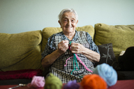 Portrait of smiling senior woman crocheting on the couch at home - RAEF02131