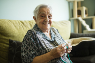 Portrait of smiling senior woman crocheting on the couch at home - RAEF02134