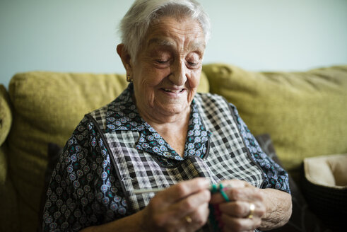 Portrait of smiling senior woman crocheting on the couch at home - RAEF02137