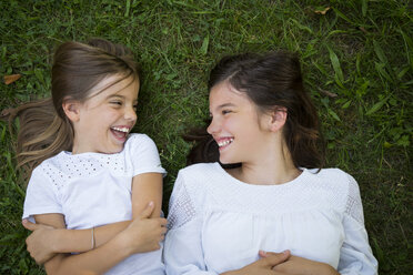 Two sisters lying together on a meadow having fun - LVF07440