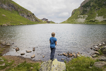 Austria, Tyrol, Fieberbrunn, Wildseeloder, girl standing at the shore of lake Wildsee - PSIF00060