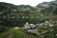Austria, Tyrol, Fieberbrunn, Wildseeloder, woman sitting at the shore of lake Wildsee next to a boat - PSIF00069