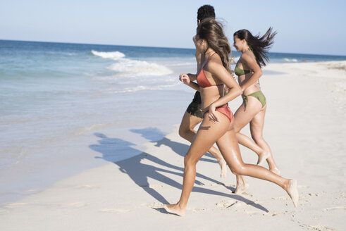 Happy carefree friends running on the beach to the sea - PACF00081