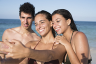 Happy friends taking selfies on the beach - PACF00090