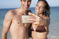 Happy young couple taking selfies on the beach - PACF00093