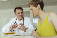Woman discussing teatment with her doctor - MFF04466