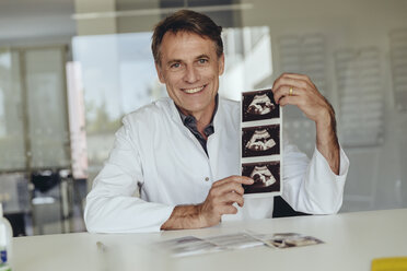 Doctor sitting at desk, showing ultrasound scan of a fetus - MFF04511