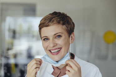 Portrait of a confident female doctor, removing surgical mask - MFF04514