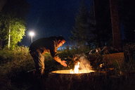 Finland, Man warming up at a camp fire on a camping ground - KKAF01727