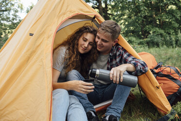 Young couple sitting in tent, drinking tea - VPIF00623