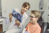 Female dentist explaining boy a x-ray image - MFF04523