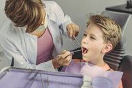 Dentist examining boy's teeth with dental instruments - MFF04529