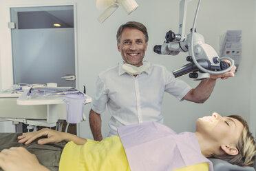 Dentist examining his patient, using dental microscope - MFF04553