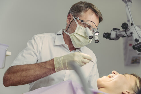 Dentist examining his patient, using dental microscope - MFF04556