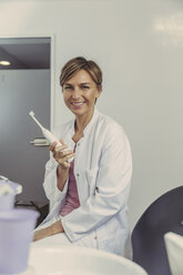 Female dentist holding electrical tooth brush - MFF04565