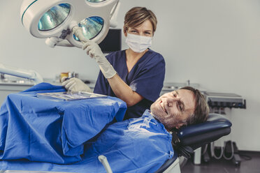 Patient smiling at dental surgeon after successful treatment - MFF04574
