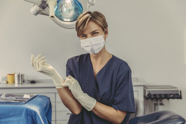 Dental surgeon wearing surgical mask, putting on surgical gloves - MFF04580
