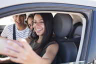 Friends having fun on a road trip, taking smartphone selfies - PACF00100