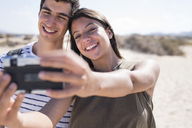 Young couple having fun on the beach, taking smartphone selfies - PACF00109