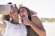 Girlfriends having fun on the beach, taking smartphone selfies - PACF00115