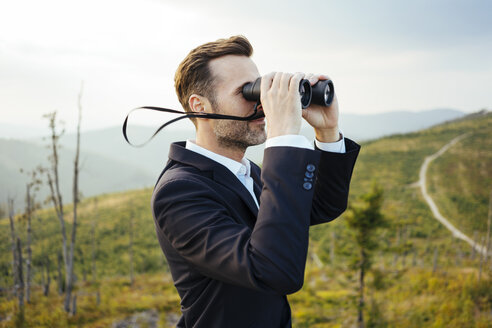 Businessman looking through binoculars on top of a mountain - BSZF00581