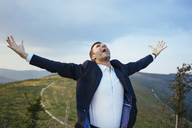 Screaming businessman standing on top of a mountain - BSZF00584