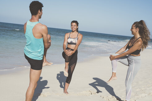Spain, Canary Islands, Fuerteventura, two young women and young man stretching on the beach - PACF00126