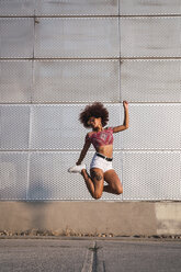 Fashionable young woman jumping in the air - KKAF01752