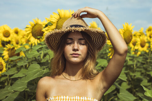 Young woman holding a straw hat on her head in a field of sunflowers - ACPF00325