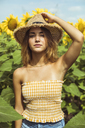 Young woman holding a straw hat on her head in a field of sunflowers - ACPF00328