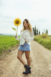Young woman on a dirt road holding a sunflower - ACPF00334