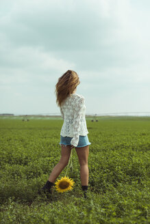 Young woman walking holding a sunflower in a green field - ACPF00337