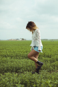 Young woman walking in a green field - ACPF00340
