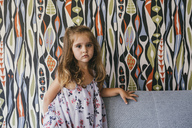 Portrait of serious little girl on couch in front of patterned wallpaper - MFF04605
