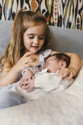 Girl sitting on couch looking at newborn baby brother - MFF04608