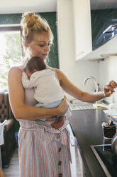Mother holding newborn baby in kitchen while making tea - MFF04611