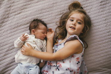 Smiling girl lying on blanket cuddling with her baby brother - MFF04620
