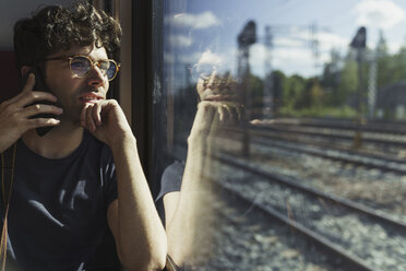 Man traveling by train talking on cell phone at the  window - KKAF01777
