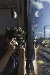 Man traveling by train taking picture with old-fashioned camera - KKAF01780