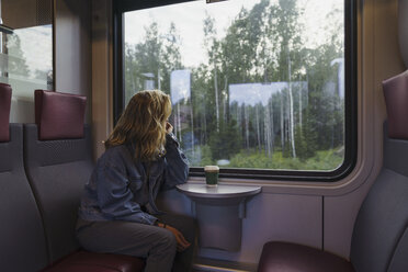 Woman traveling by train looking out of window - KKAF01783