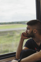 Man traveling by train looking out of window - KKAF01786
