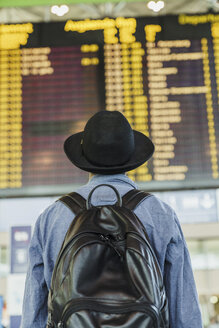 Young man with hat and backpack looking at arrival departure board at the airport - KKAF01789