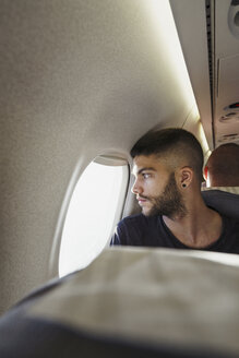 Young man in a plane looking out of window - KKAF01795