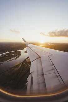 View out of window on wing of a plane at sunset - KKAF01801