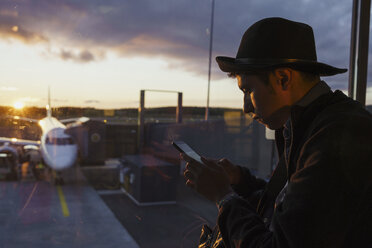 Young man using cell phone at the airport at sunset - KKAF01804