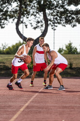 Three young men playing basketball on an outdoor court - STSF01739