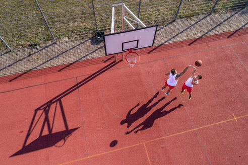 Two young men playing basketball on an outdoor court, aerial view - STSF01742