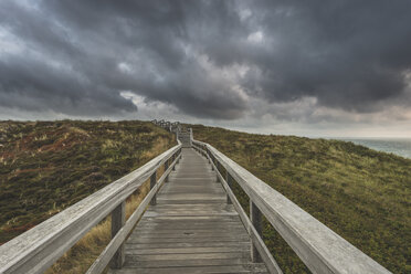 Germany, Schleswig-Holstein, Sylt, Wenningstedt, boardwalk to the beach under rain clouds - KEBF00919