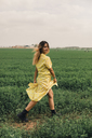 Young woman walking in a green field - ACPF00342