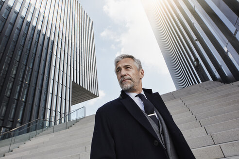 Portrait of fashionable businessman in front of modern architecture - RORF01466